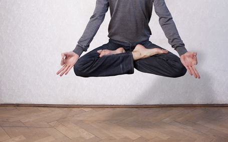 A young man levitating in yoga position, meditation
